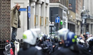 A protester looks on as riot police surround the building in London's West End