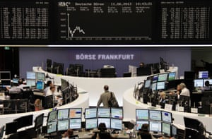 Traders work at their desks in front of the DAX board at the Frankfurt stock exchange June 11, 2013.