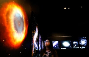 Visions of the universe: A museum employee looks at one of the one hundred plau images of space on d