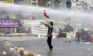 A protester is hit by a water cannon during clashes with riot police in Istanblu's Taksim square