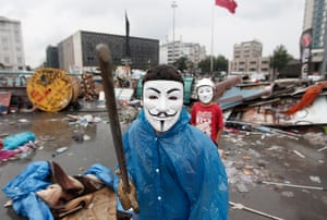 Turkey update: A boy wearing a Guy Fawkes mask displays a wooden sword behind a barricade