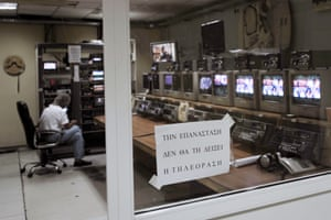 "A Greece's public TV technician sits in an editing room where placard reads in Greek ""the revolution won't be televised"" at the ERT headquarters in Athens on June 12, 2013, a day after a shock decision by the government to shut down the state broadcaster's operations with immediate effect, a move affecting nearly 2,700 jobs."