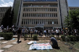 A protester prepares a banner outside the ERT state broadcaster headquarters in Athens' suburb on June 12, 2013 .