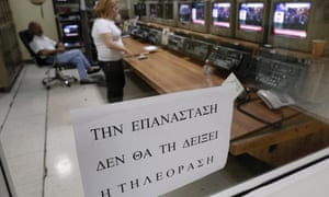 "Employees work at a control room of the Greek state television ERT headquarters in Athens June 12, 2013. The sign reads: ""The revolution will not be televised."""