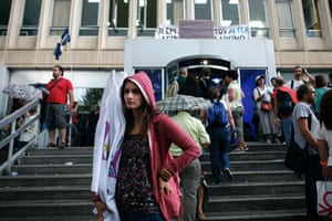 A protester stands at the entrance of the headquarters of Greek state broadcasting station ERT after the government announced its closure, in Athens, Greece, 12 June 2013.