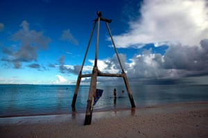 Kiribati, Pacific island: Binata Pinata stands on top of a rock underneath an old tower. The tower us