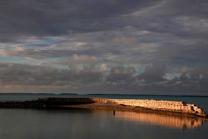 Kiribati, Pacific island: A man swims next to a manmade wall built to protect the island from rising