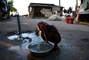 Kiribati, Pacific island: A boy washes himself with water from a well outside his home in the village