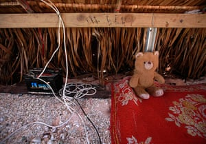 Kiribati, Pacific island: A toy bear sits next to a battery storing solar power in the home of Binata