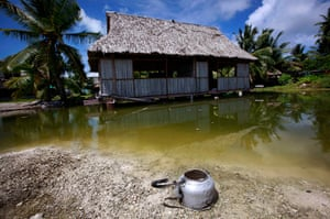 Kiribati, Pacific island: An abandoned house that is affected by seawater during high-tides stands ne