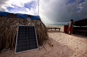 Kiribati, Pacific island: Binata Pinata checks the roof of her home as a storm approaches Bikeman isl