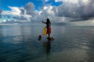 Kiribati, Pacific island: Binata Pinata stands on top of a rock holding a fish her husband Kaibakia j