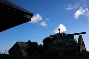 Kiribati, Pacific island: A boy stands on top of an old World War Two cannon, used by the Japanese, n