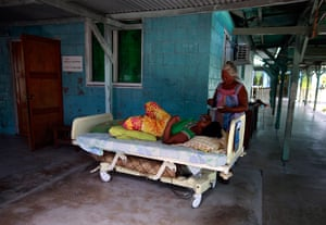 Kiribati, Pacific island: A woman prepares to feed a patient on a bed, placed outside due to lack of
