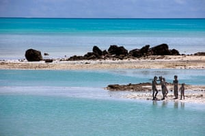 Kiribati, Pacific island: Young boys cover each other in reef-mud