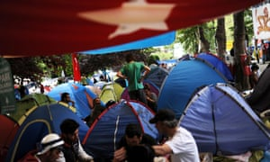 Anti-government protesters are sitting near their tents in Gezi Park in Istanbul on 13 June 2013.
