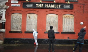 Young people play football against a boarded-up pub in Gorton
