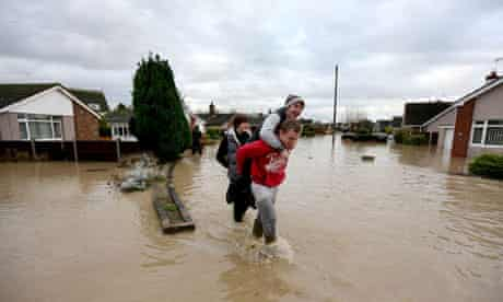 Residents of St. Asaph, Denbighshire, North Wales make their way through flood waters