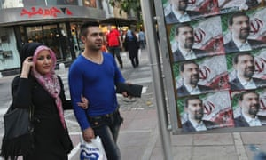 Iranians walk past posters of the presidential candidate Mohsen Rezaei, a former Revolutionary Guard commander.