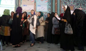 Iranian women wait in line to cast their vot at a polling station during the Iranian presidential elections in Tehran.