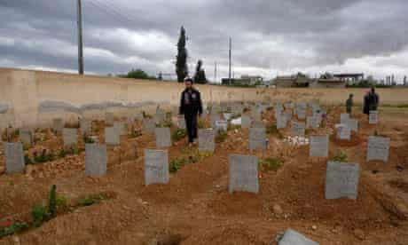 Men visit the graves of people whom activists say were killed by forces loyal to Assad, in Qusair