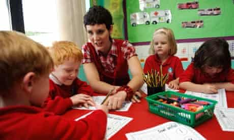 Young woman teacher in primary school teaching mathematics to young children, Wales UK