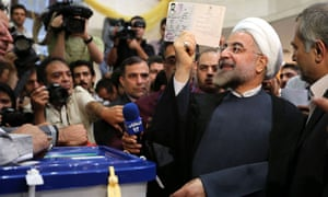 Iranian presidential candidate Hassan Rouhani raises his identity card before casting his vote