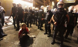 A demonstrator is surrounded by riot police in Istanbul.