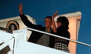 Barack Obama and first lady Michelle Obama wave as they depart Joint Base Andrews in Washington for their flight to Northern Ireland.