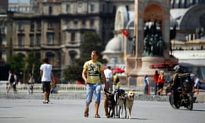 A man walk dogs in a quiet Taksim Square in Istanbul after Turkish police detained 441 people in connection with clashes there on Sunday.