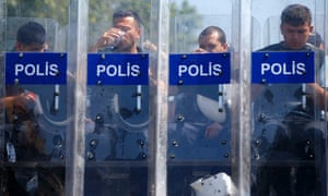 Turkish police take a break as they guard the entrance of Gezi Park at Taksim Square.