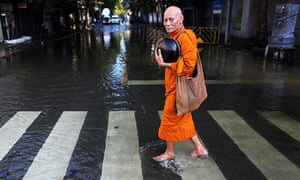 A Buddhist monk walks in a flooded street to collect alms outside the Grand Palace in Bangkok