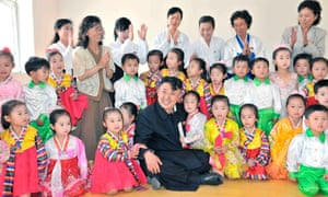 North Korean leader Kim Jong-un gets down with the kids during a visit to a machine factory run by Huh Chul-yong in this undated photo released today by the country's Korean Central News Agency.