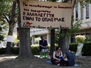"""Supporters of the employees of state broadcaster ERT sit outside its headquarters in Athens June 17, 2013. The banner reads, """" Let's turn off the government's switch. Solidarity is our weapon""""."""