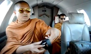 Screengrab from YouTube of monk with aviator sunglasses, branded travel bag and wireless headphones
