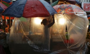 On another weather front a fruit vendor fixes a plastic sheet to protect her produce during a downpour in Manila in the Philippines .