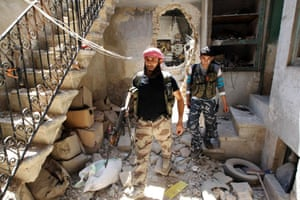 Members of the Free Syrian Army walk through the rubble of damaged buildings in the Bab al-Nasr neighborhood of Aleppo.