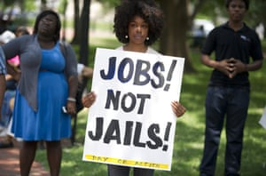 "A demonstrator holds a sign during a rally calling on Barack Obama to end the ""war on drugs"", which campaigners say leads to mass incarceration of African Americans, during a Day of Direct Action event in Lafayette Park in Washington."