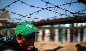 A Young Palestinian crawls under barbed wire during a summer physical training camp run by Hamas in Gaza City.