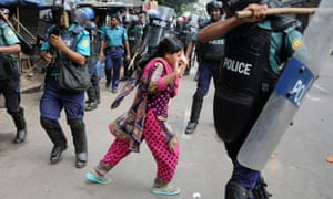 A protester tries to escape as Bangladeshi police use sticks to disperse striking garment workers in Dhaka. Police fired rubber bullets and teargas at thousands of garment workers who were protesting for better benefits in the capital.