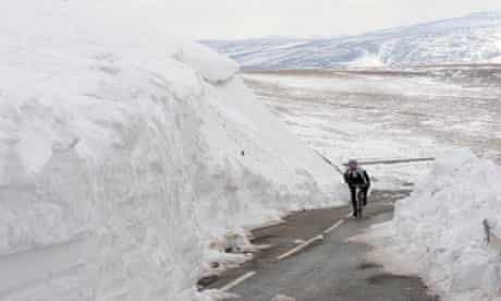 A cyclist rides alongside large snow drifts on the edge of the Peak District National Park in spring