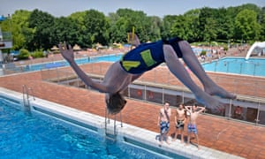 A boy jumps into the water during the hottest day of the year so far at a public pool in Essen, Germany.