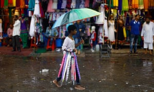Preparing for the monsoon. A young Indian boy sells umbrellas as it rains in a market in Mumbai, India. The monsoon rains which usually hit India from June to September are crucial for farmers whose crops feed hundreds of millions of people.