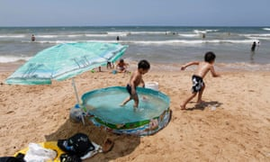 Syrian children play in an inflatable pool to cool themselves from the summer heat at Ramlet al- Baida beach in Beirut, Lebanon.