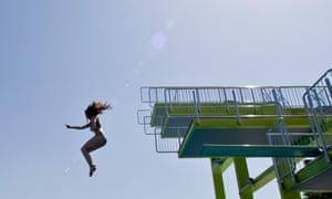 Fun in the sun. A young woman jumps off a diving platform at open-air swimming pool Westbad in Nuremberg, Germany as warm weather continues.