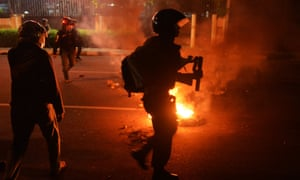 Indonesian police look on after dispersing student protesters with tear gas during a protest againt fuel price hikes in Jakarta.