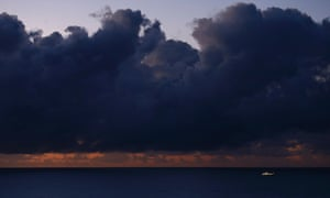 A boat is seen under an imposing sky at sunrise off the coast of Boa Viagem Beach in Recife, Brazil.
