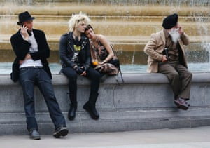 A couple sit together as two men use their mobile phones by a fountain in Trafalgar Square in London.
