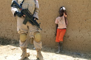 A young boy watches a United Nations peace keeper in the North Darfur state capital of El-Fasher. Eltigani Seisi, the head of the Darfur Regional Authority has said that traditional mediation techniques involving tribal elders are no longer effective.
