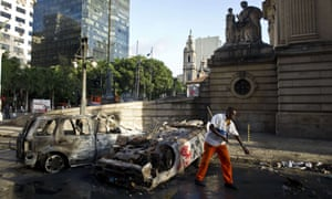 A municipal worker sweeps the streets by two cars burnt down by demonstrators on the eve  in downtown Rio de Janeiro, Brazil. Police fired tear gas and rubber bullets in clashes with protesters yafter tens of thousands rallied in major Brazilian cities against the huge costs of hosting the 2014 World Cup.